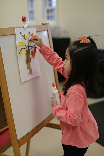 Child creating an artwork during a school group visit
