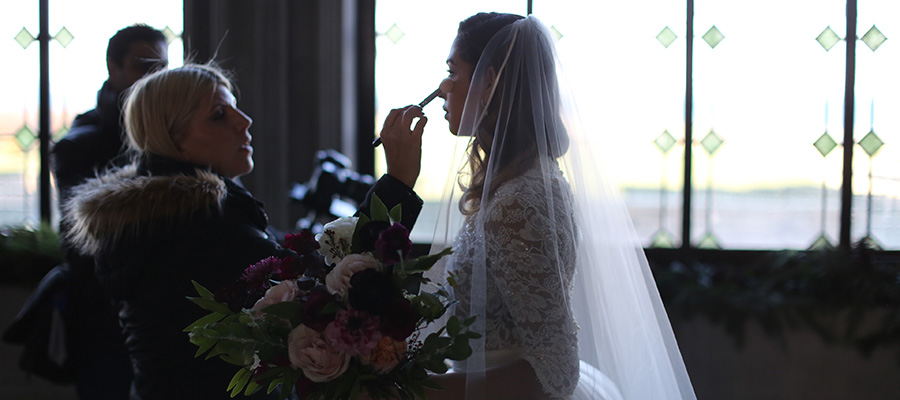Makeup artist touching up bride