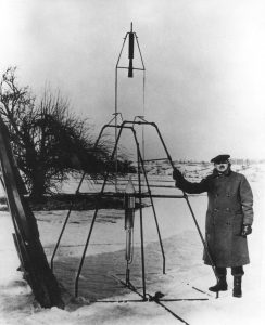 Goddard next to early rocket prototype