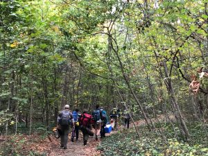 Wildnerness Survival students walking through the woods to the camp ground